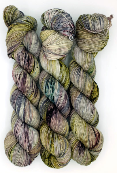 Heather gray indie dyed yarn speckled with spring green and moody purple, inspired by the misery on the moors in Charlotte Bronte's Wuthering Heights.