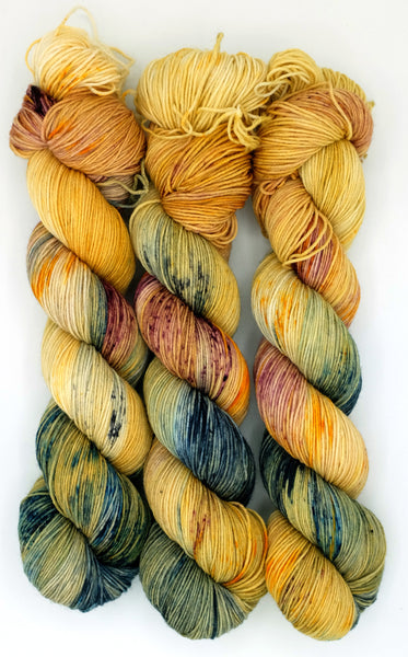Goldenrod indie dyed yarn dramatically speckled with indigo, berry, and black accents inspired by the unforgettable feminist tale, The Yellow Wallpaper.