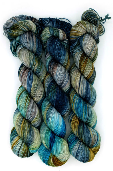 Densely variegated indie dyed yarn in hues of ochre, midnight blue, cerulean, and burgundy inspired by the mind-boggling novel by Mark Z. Danielweski.