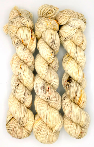 A cream indie dyed yarn with rust and sienna speckles inspired by age-induced spots on book pages.