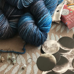 Several stone stitch markers with an assortment of tea, and moon stickers near a stack of gray and classic blue yarn skeins