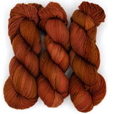 A rustic burnt orangw hand dyed yarn with charcoal speckles