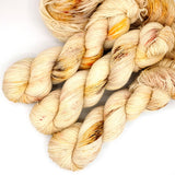 Rust, marigold, and umber speckled neutral cream yarn.