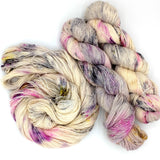 White yarn with fuchsia, gray, and bright green speckles.