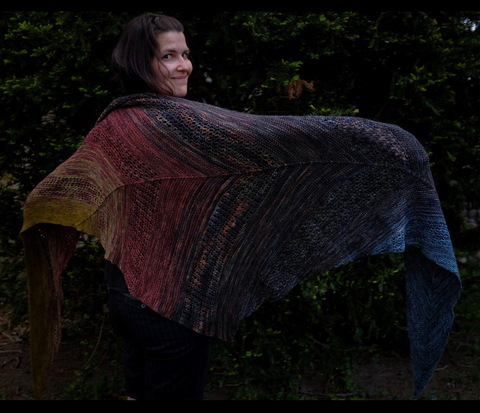 Dyer Rita poses against a dark forest background with her Find Your Fade shawl in a dark and moody rainbow of yarns from many different dyers.