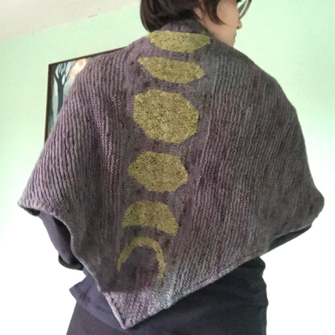 Rita wears her finished Lunar Spine Shawl and faces away from the camera.