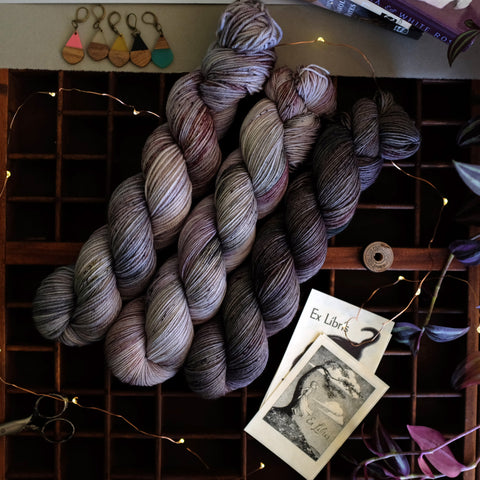 Moody wisteria hues speckled with deep green, rich burgundy, and more grays, near bookplates and the work of Joyce Carol Oates.