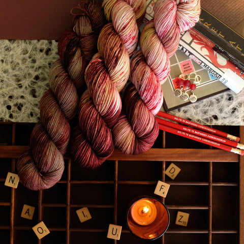 Red variegated yarn with blush and peach hues inspired by Margaret Atwood's work, amongst scrabble tiles, Atwood books, and themed extra gifts.