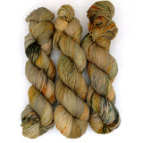 A variegated amber yarn dappled with blue-gray, covered in thick forest, gray, and marigold speckles.