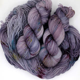 Wisteria hued yarn heavily speckled with aqua, magenta, slime green, and wine colors.