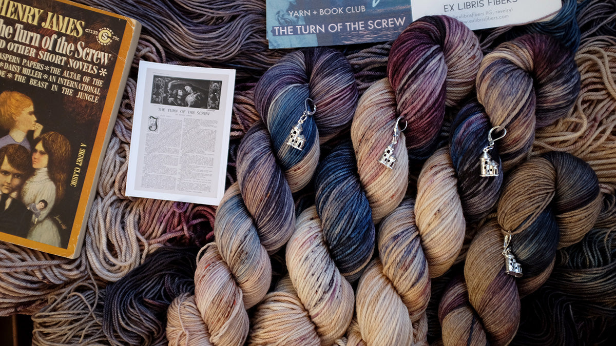 Turn of the Screw inspired hand dyed yarn shown with stitch marker and sticker and copy of the book