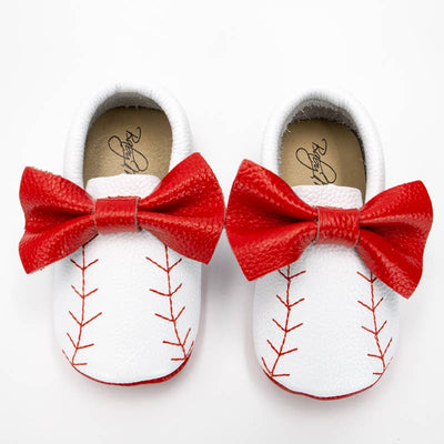 The perfect shoes for the baseball loving babes in your life! White baby moccasins with red baseball sticking, finished off with a red bow.