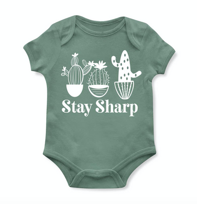 Super fun green colored graphic bodysuit onesie featuring cactus graphics and white bold font reading Stay Sharp