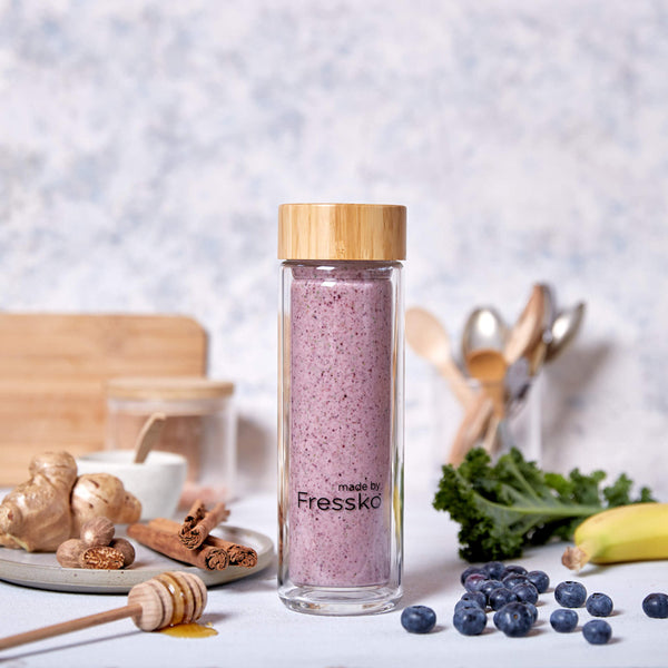 Berry smoothie in Fressko glass flask surrounded by kale berries and honey