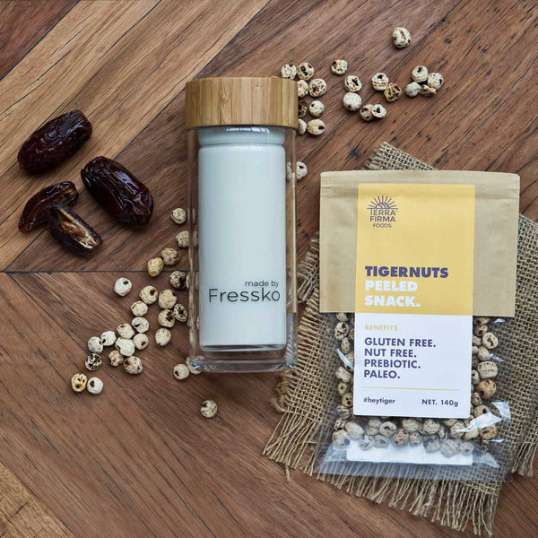 Tigernut Mylk Smoothie in glass fressko flask surrounded by dates and tigernuts