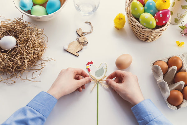 person creating easter decorations surrounded by craft equipment