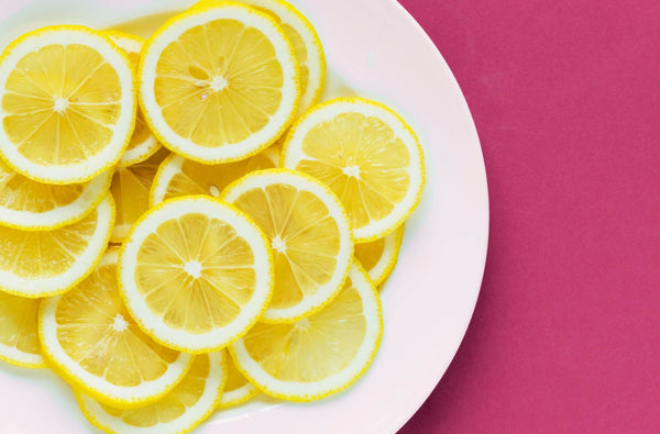 Lemon on a white plate with pink background