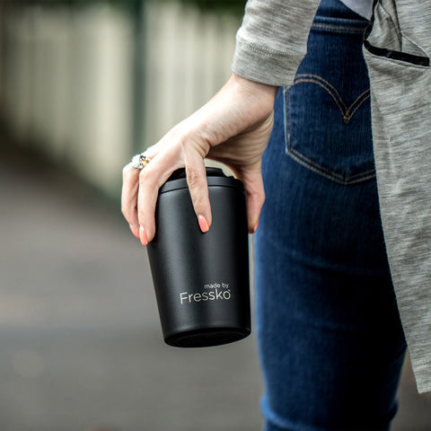 Woman holding Fressko reusable coffee cup