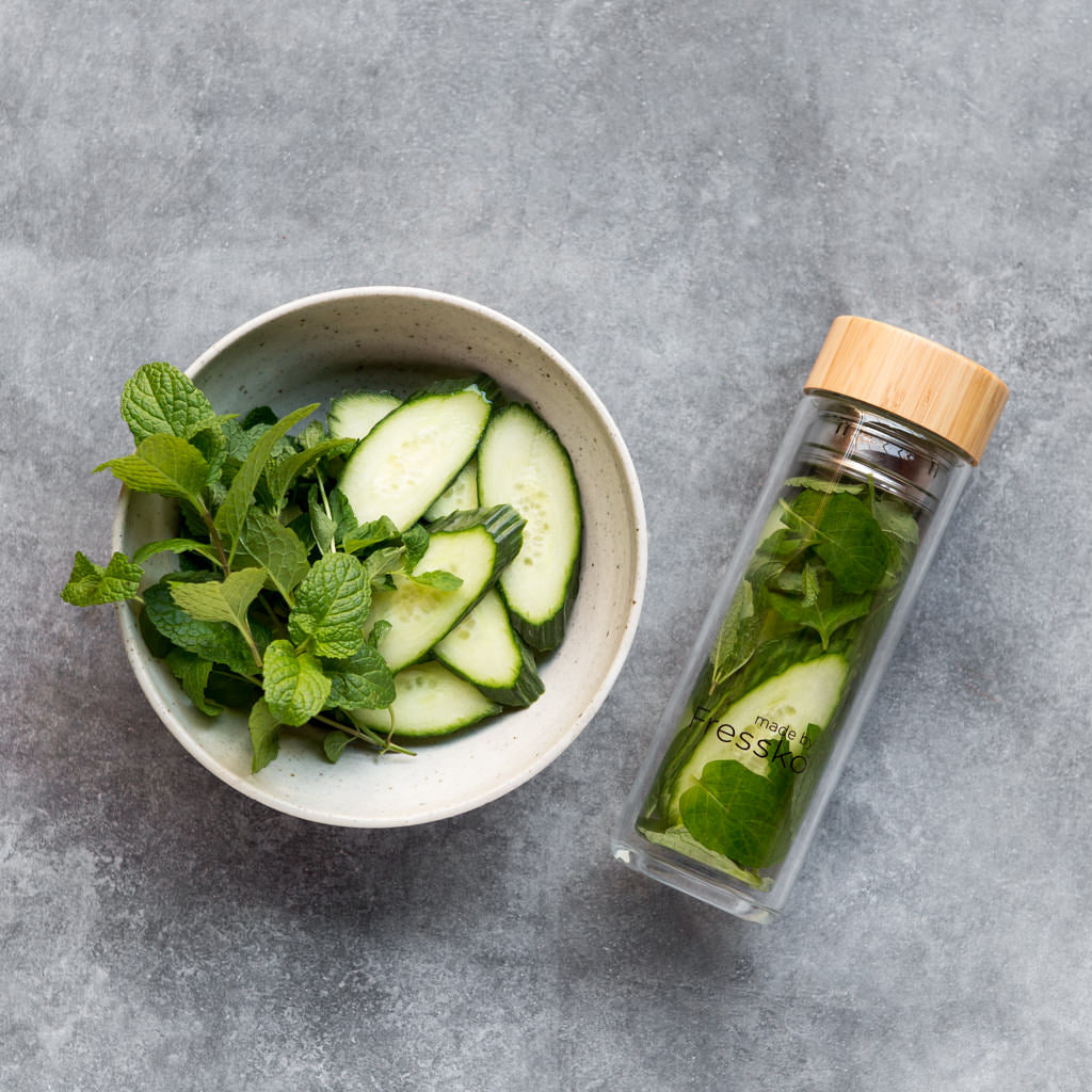 Water infusion in Fressko glass flask with bowl of cucumber and mint next to it