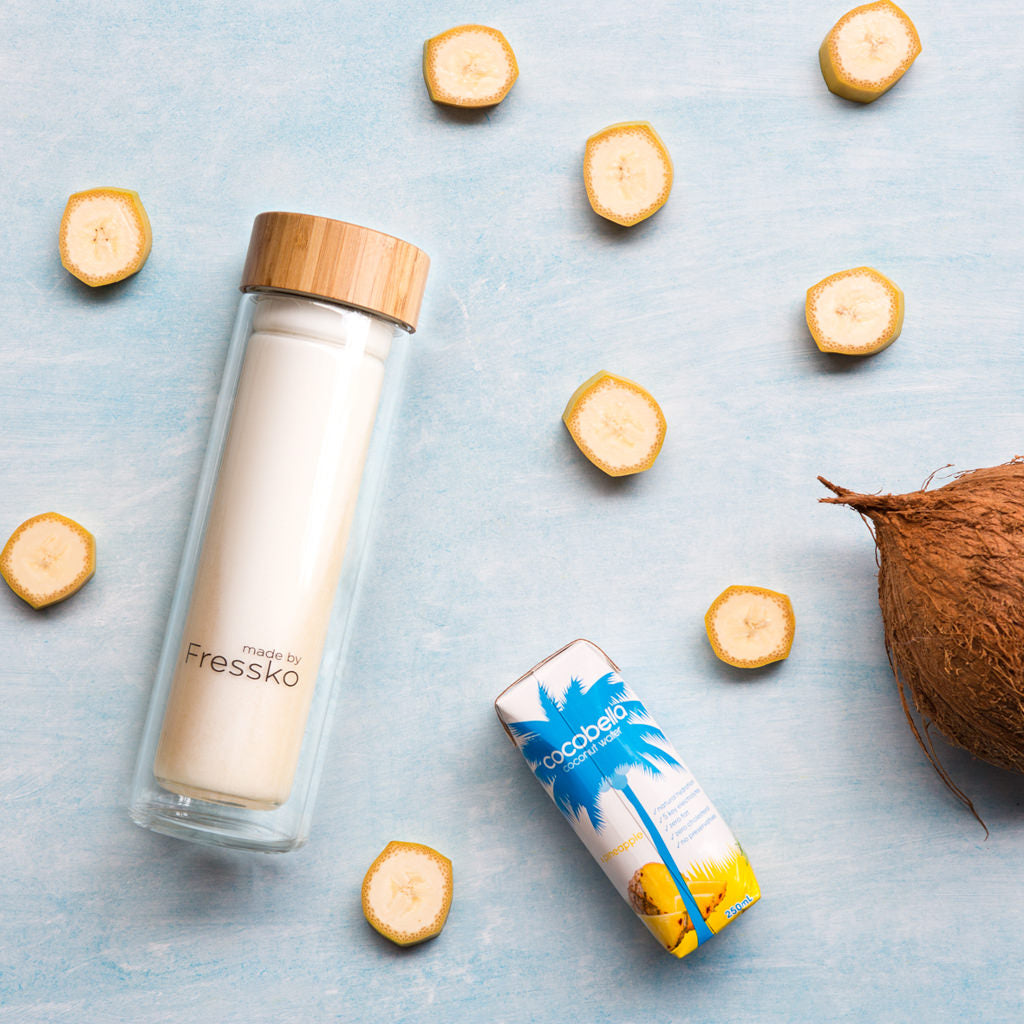 Pina colada smoothie inside fressko flask surrounded by coconut water banana and coconut
