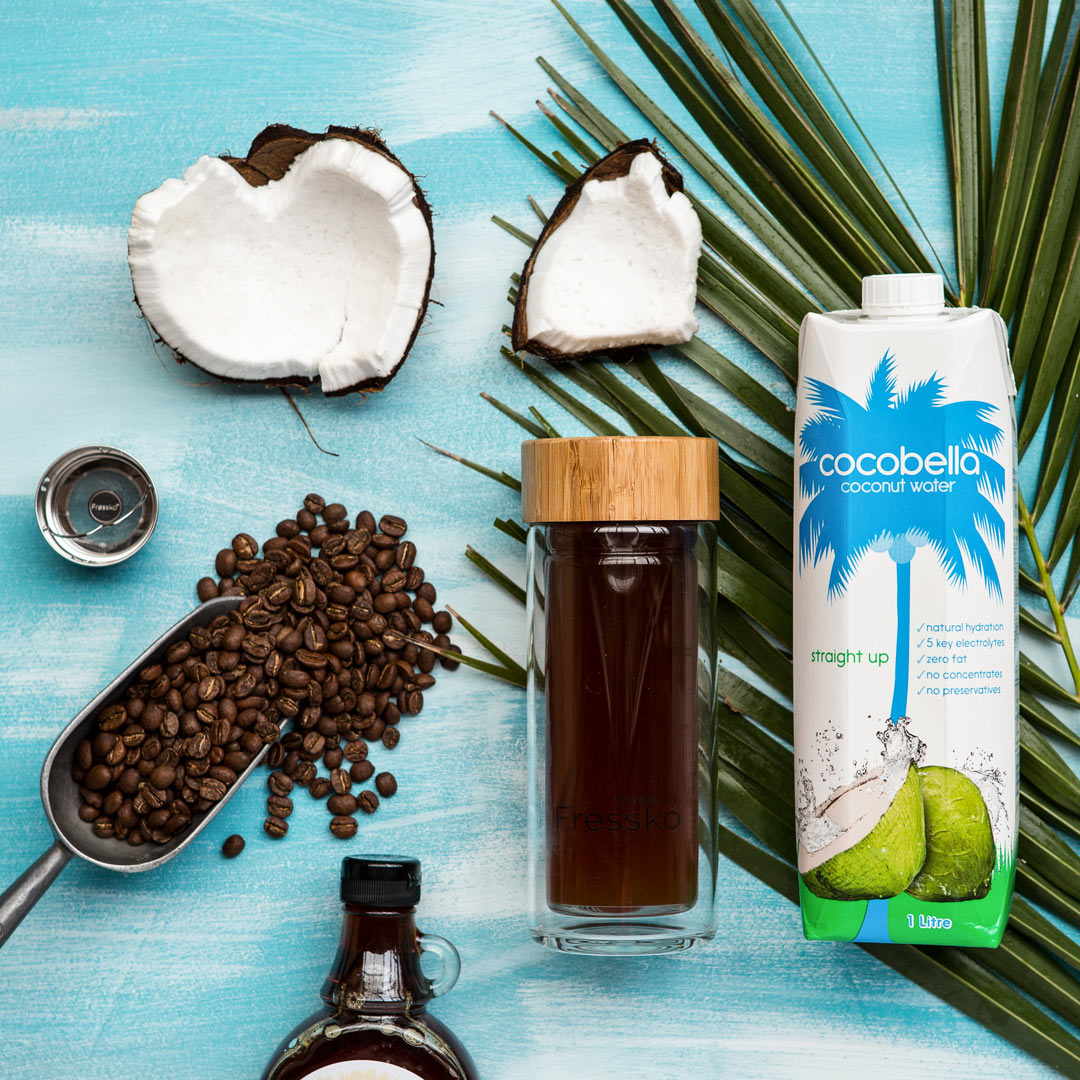cocobella coconut water coffee anc cocnut surrounding a fressko glass flask filled with coffee