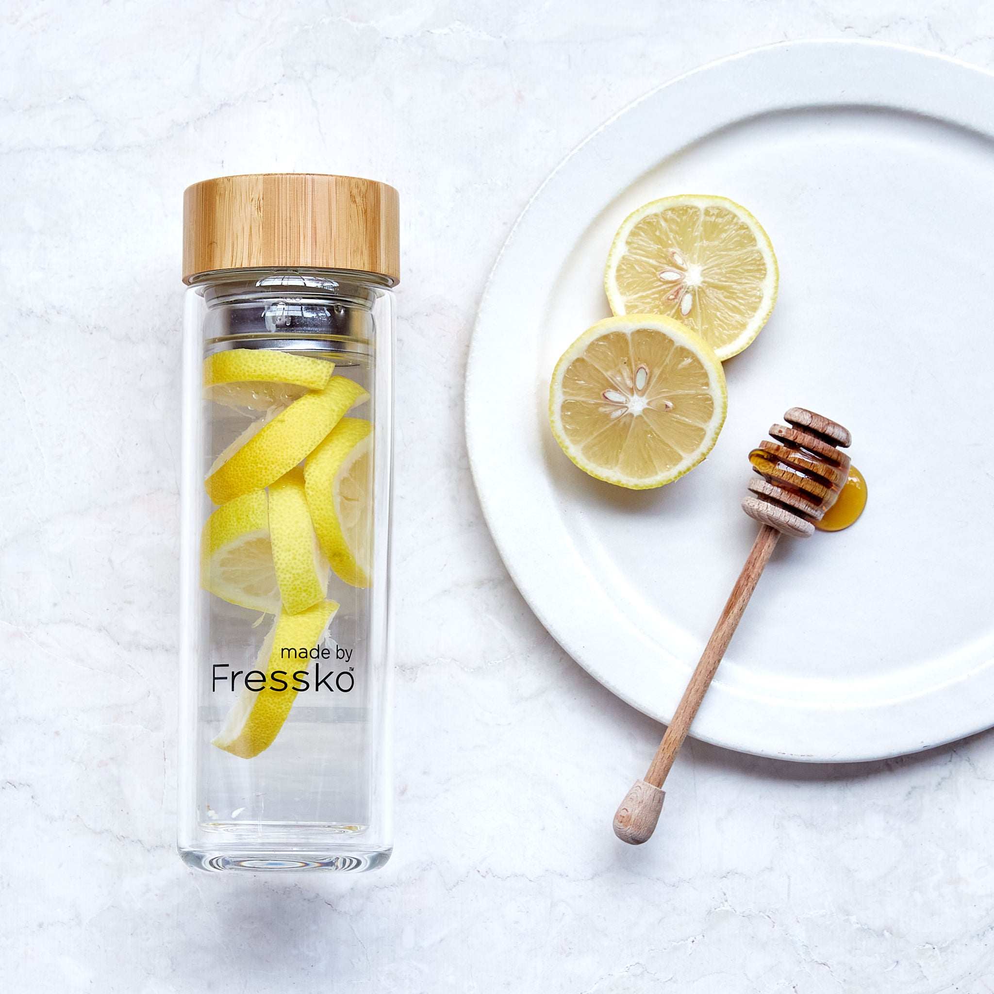 Lemon and honey water in glass fressko flask with plate with lemon and honey next to it