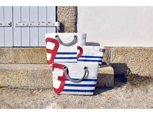 With its blue stripes and red number, this chic and practical tote bag has been sewn by hand from recycled sails and has been designed for lovers of all things nautical and French with a strong sense of style.
