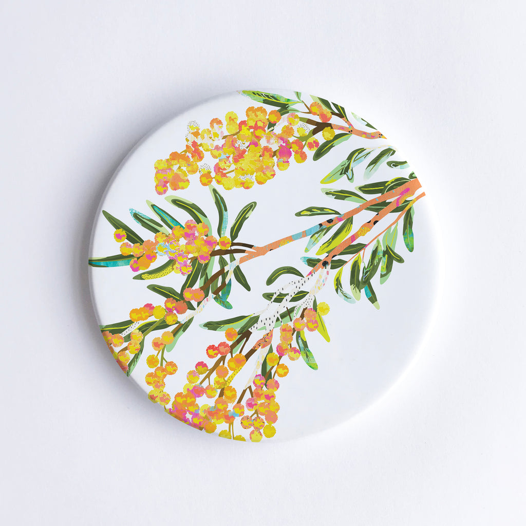 Round white ceramic coaster with a yellow, orange, green Acacia flower illustration.