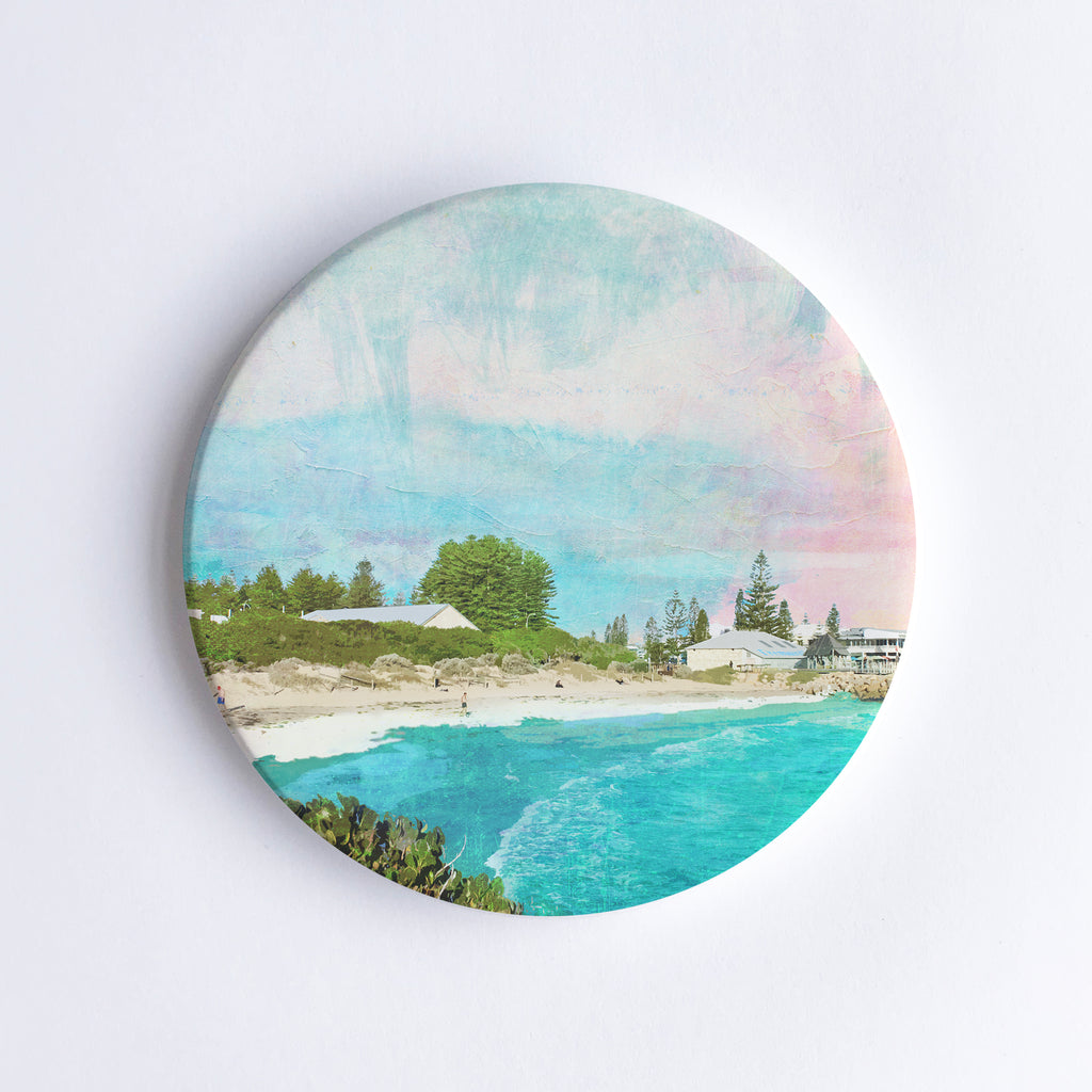 Round, hand printed ceramic coaster with illustration of Bather's Beach in Western Australia with turquoise water, sand dunes, buildings and trees.