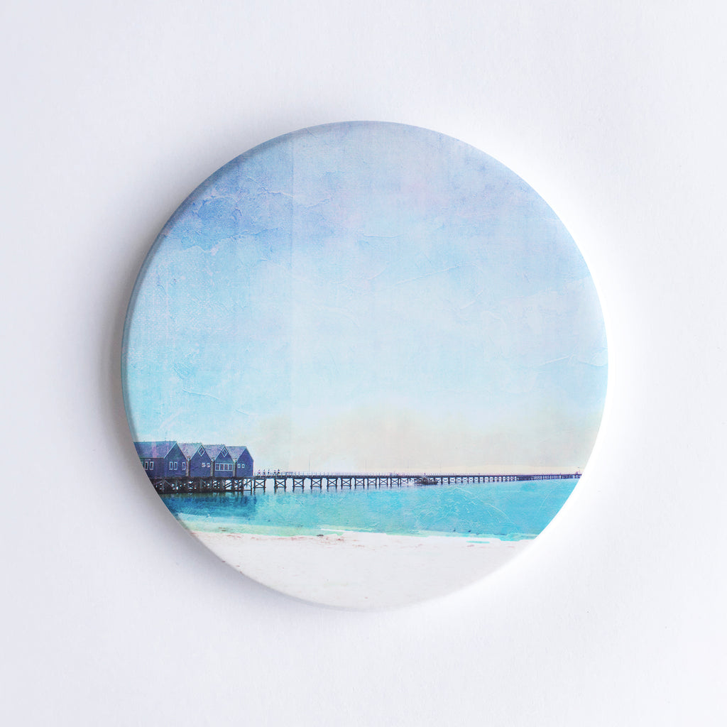 Round hand printed ceramic coaster with illustration of Busselton Jetty which consists of 4 boathouses on a 1.8km timber jetty over the ocean.