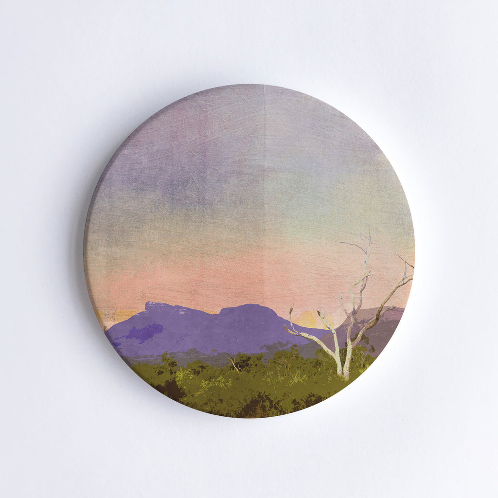 Round, hand printed ceramic coaster with illustration of a purple shining Bluff Knoll mountain during sunset with a bare tree and trees in the foreground.