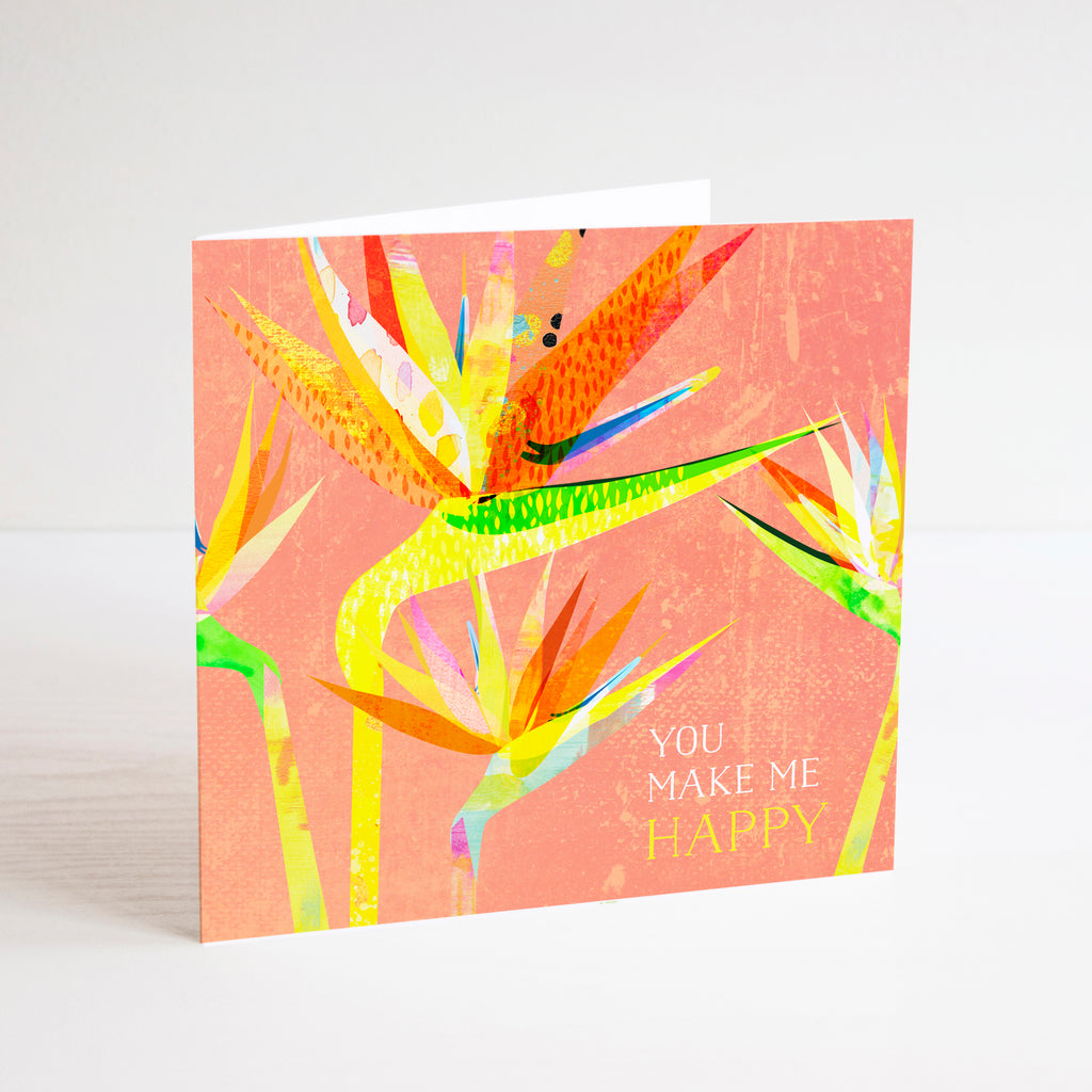 You make me happy greetings card with colourful bird of paradise flower illustration on a peach colour background.