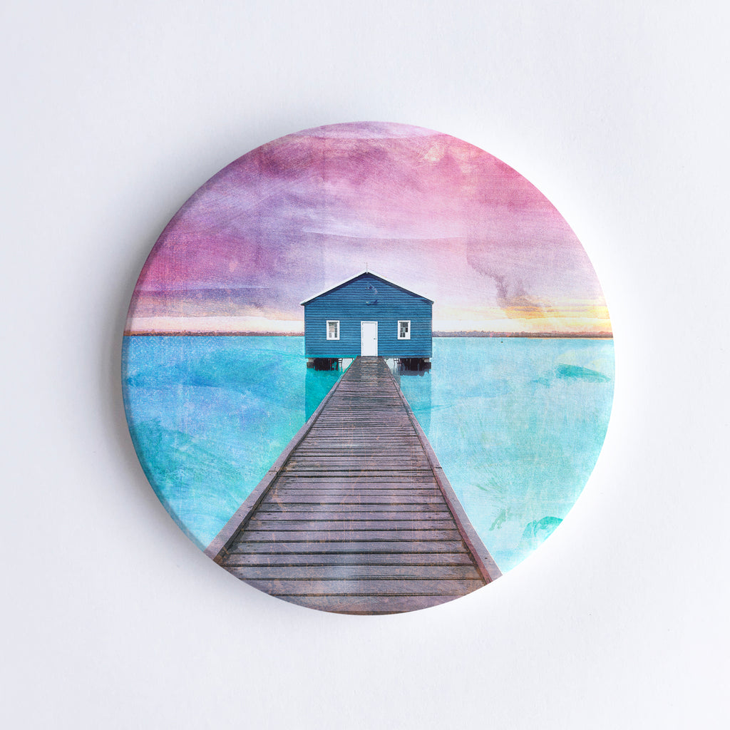 Round hand printed ceramic coaster with illustration of the blue Crawley Boathouse at the end of the pier with turquoise water and pink sky.