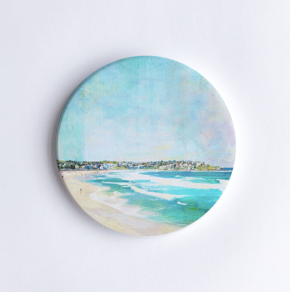 Round, hand printed ceramic coaster with illustration of Bondi Beach in Sydney showing waves and houses on a hill in the background.