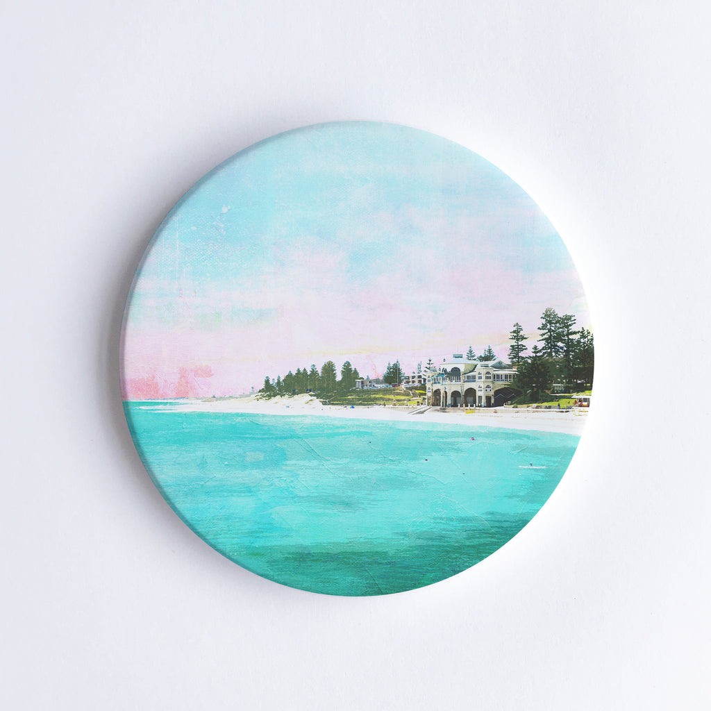 Round, hand printed ceramic coaster with illustration of Cottesloe Beach and the Indiana teahouse surrounded by trees during sunset.