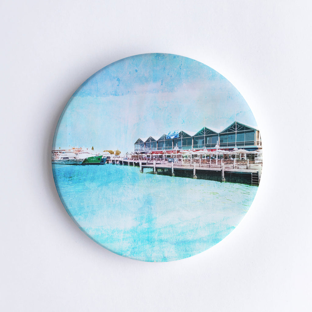 Round, hand printed ceramic coaster with illustration of Fremantle Fishing Boat Harbour and a fish restaurant on stilts over the water.