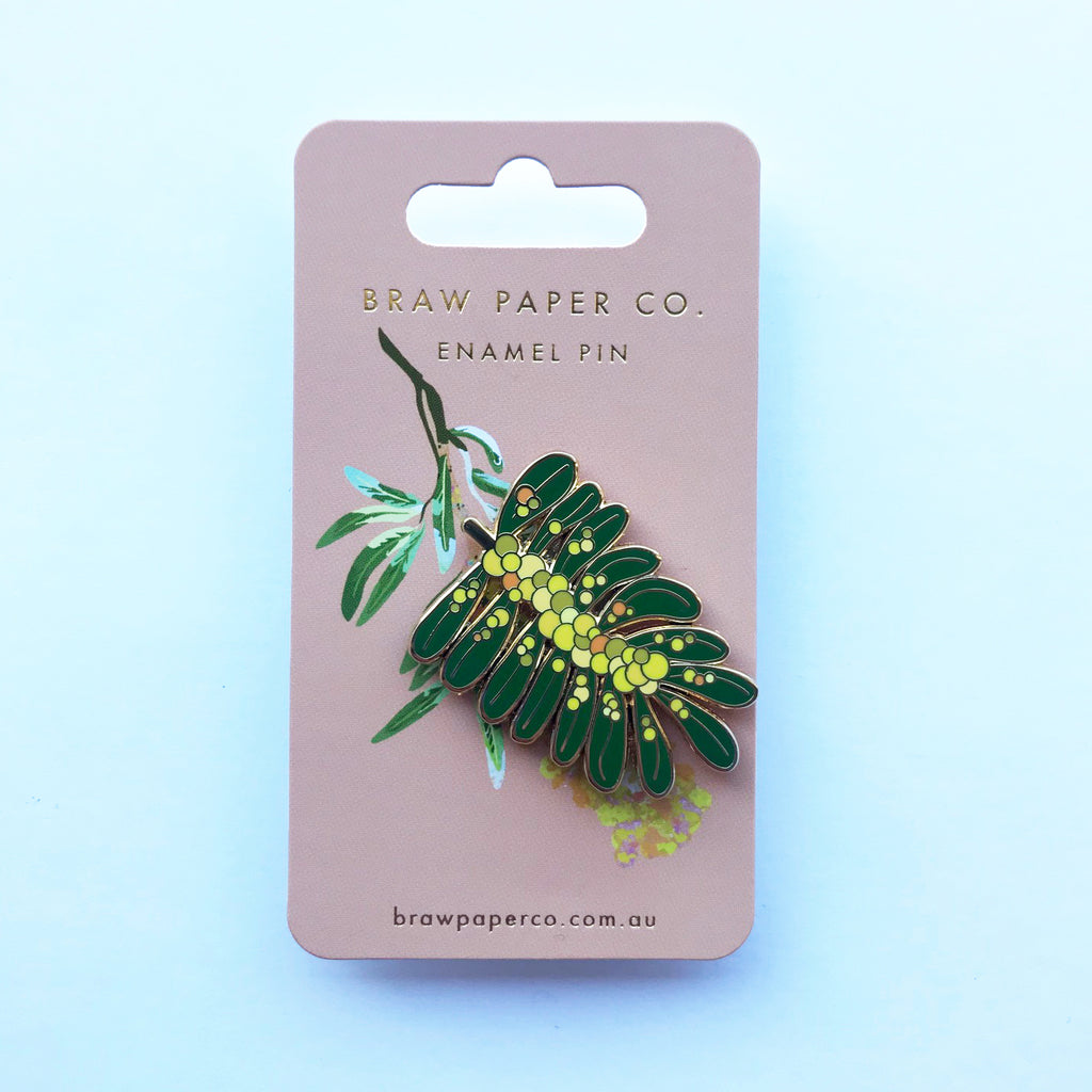 Enamel pin with yellow and green Acacia flower illustration.