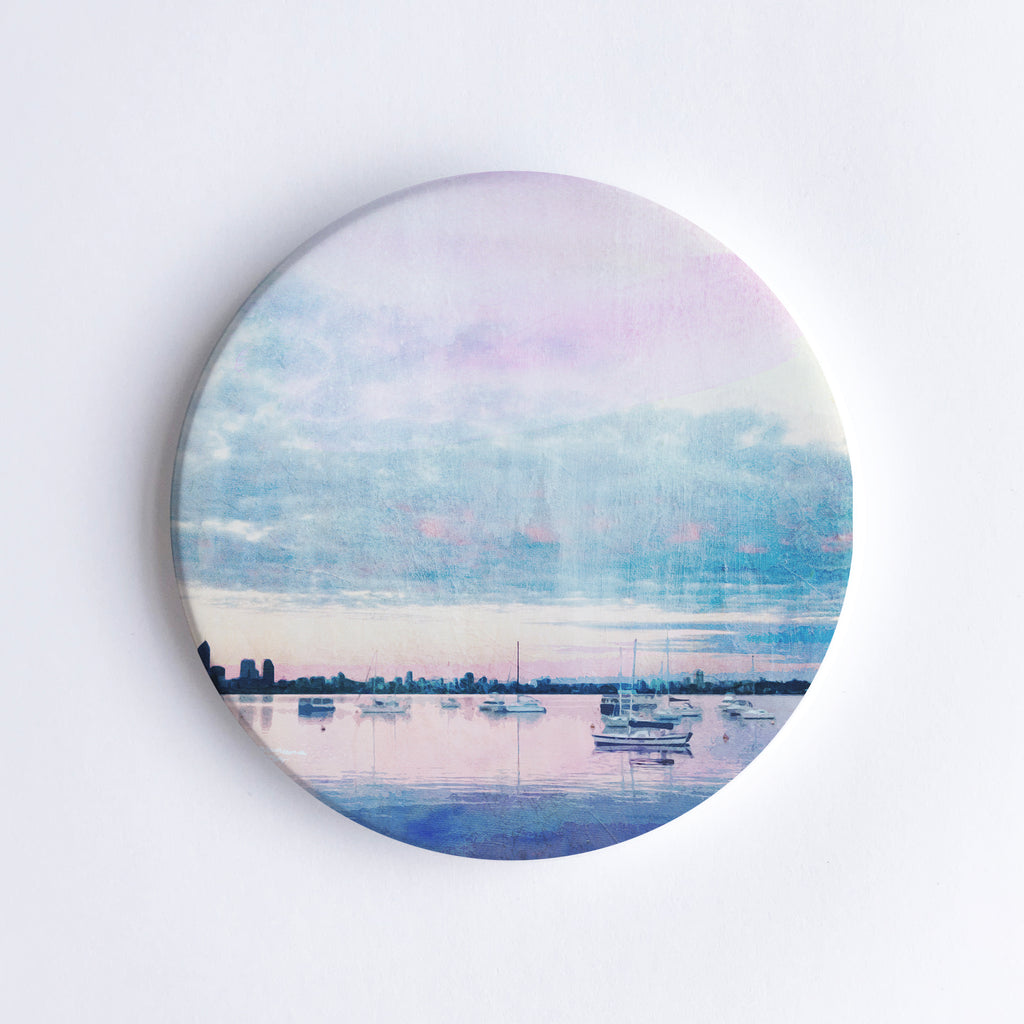 Round, hand printed ceramic coaster with illustration of Matilda Bay at dusk, sailing boats on Swan River and Perth city skyline in the background