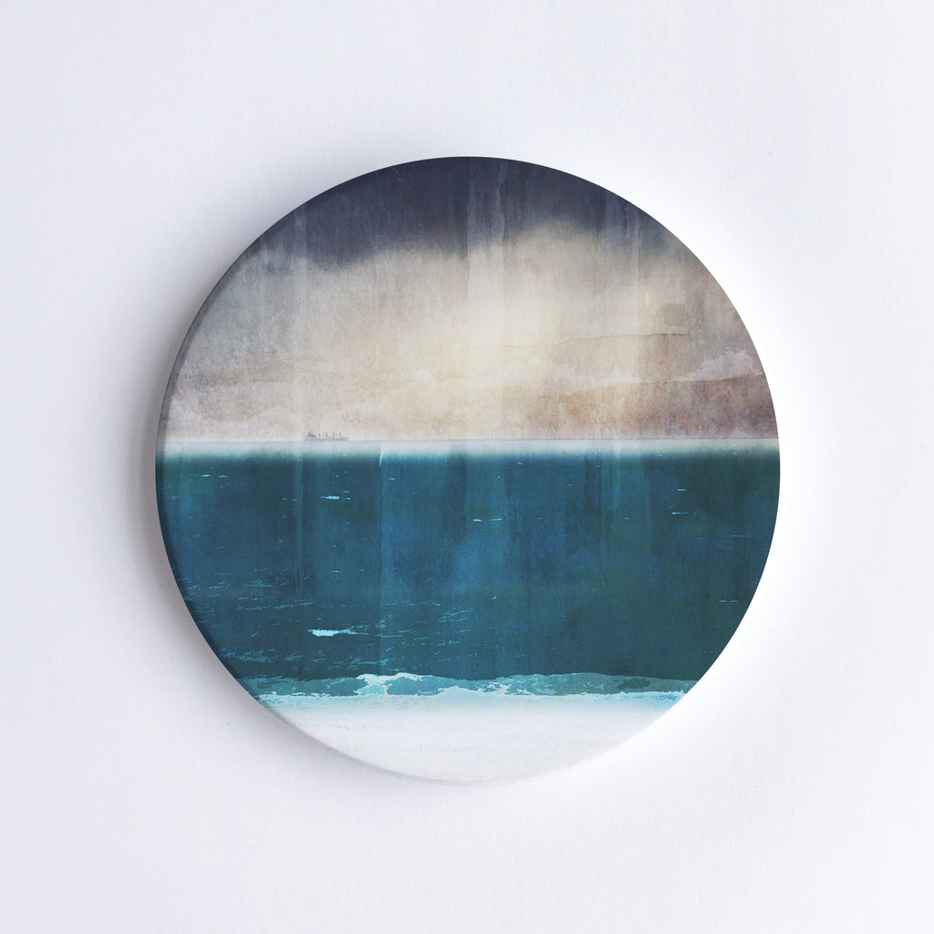 Round, hand printed ceramic coaster with illustration of Port Beach in Western Australia with dark, moody sky before a storm.