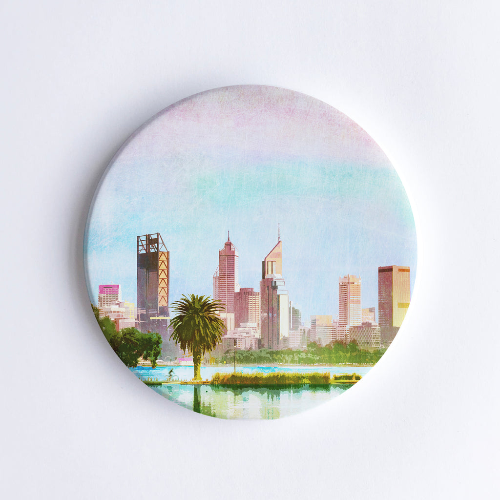 Round, hand printed ceramic coaster with illustration of Perth city skyline behind a palm tree.