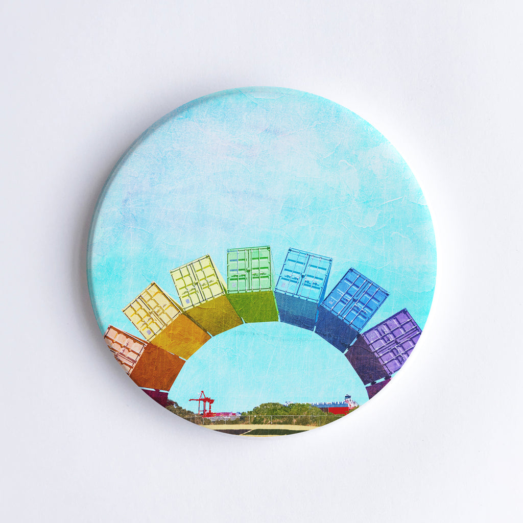 Round, hand printed ceramic coaster with illustration of Fremantle Rainbow Shipping Containers and Fremantle Harbour with cranes and a cargo ship in the background.