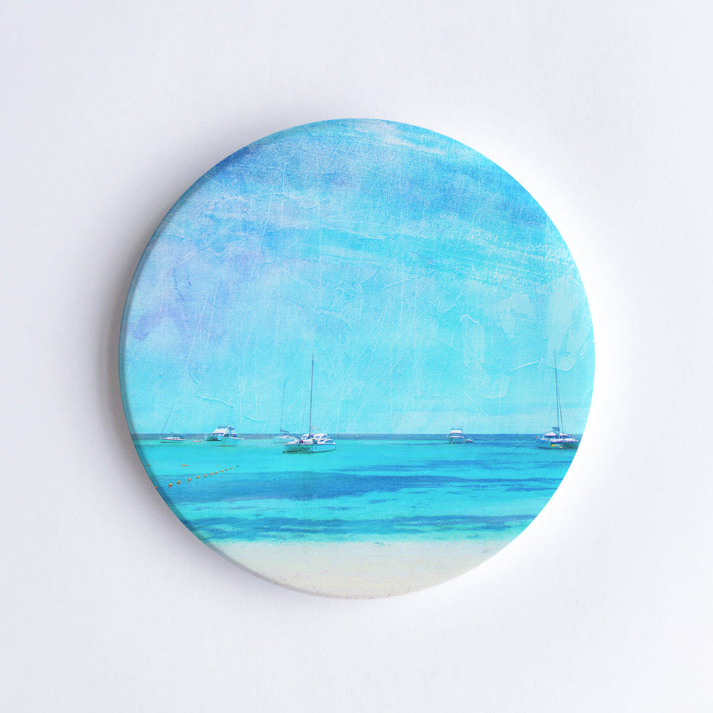 Round, hand printed ceramic coaster with illustration of Rottnest Island with sailing boats in the turquoise sea.