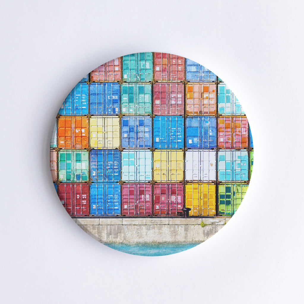 Round, hand printed ceramic coaster with illustration of colourful shipping containers at Fremantle Harbour stacked on top of each other.