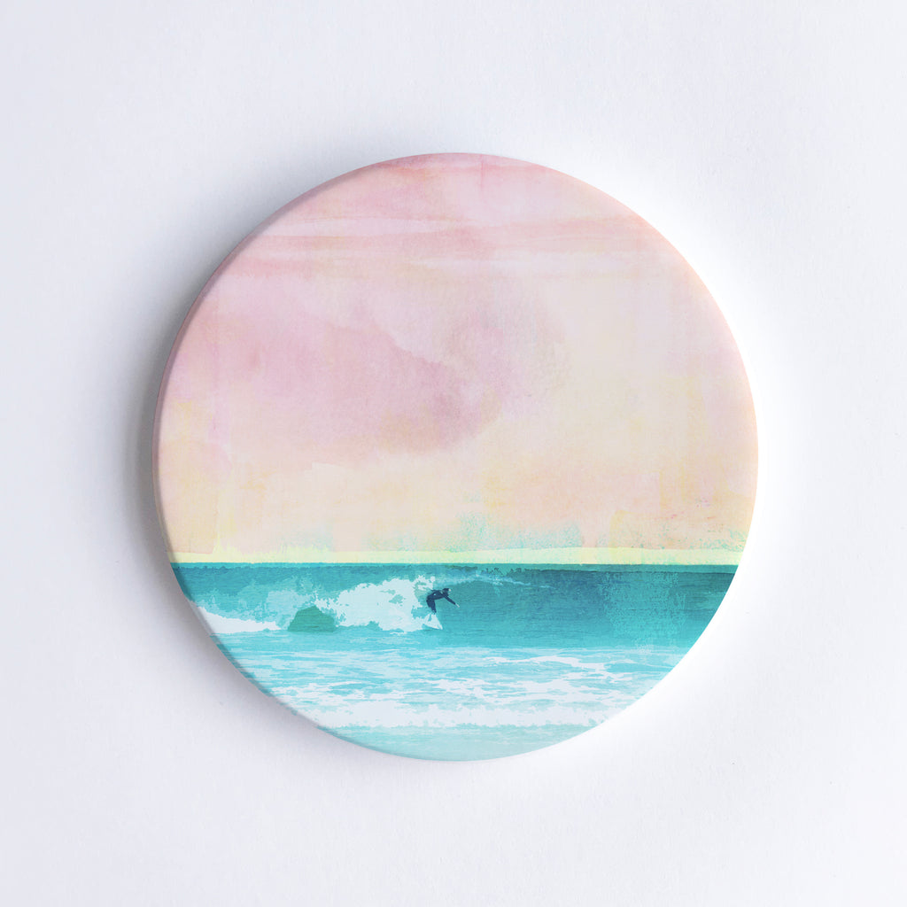 Round ceramic coaster with  an illustration of a solo surfer riding a wave at sunset.