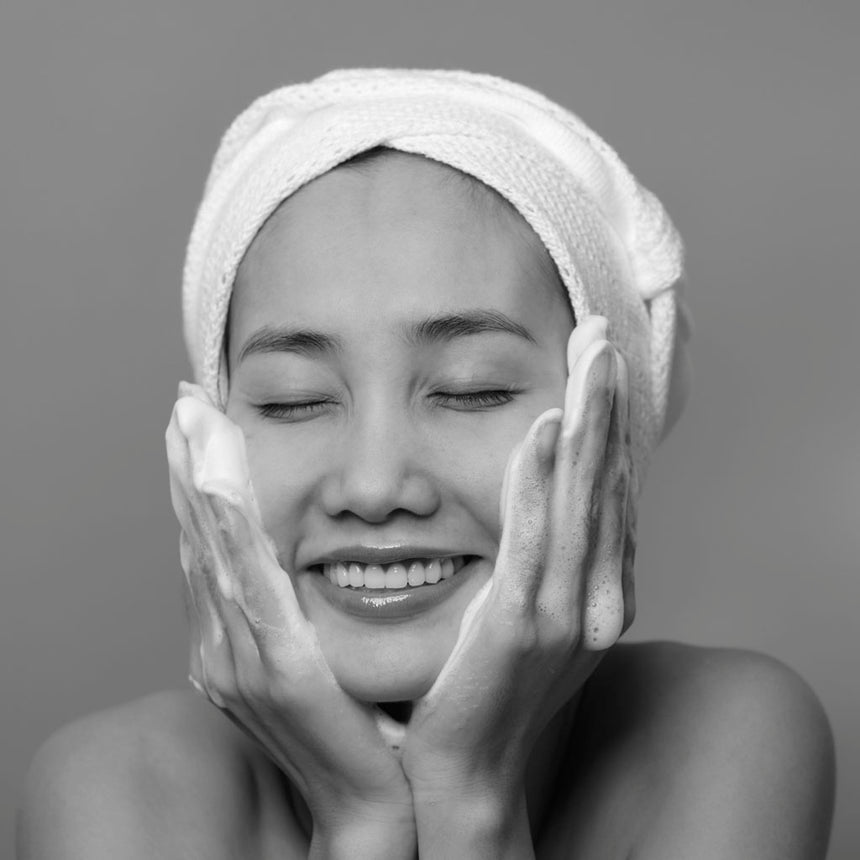 black and white close up photo of a smiling woman, whit her eyes closed, while having her hands lathered with soap on each side of her face. Representing happiness of self care.