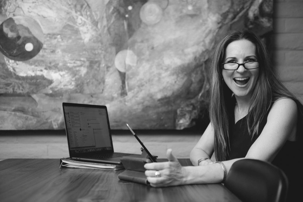 BW photo of Kathryn Mitchell sitting at a table with her computer. A large abstract celestial painting is in the background. She is in profile but turning her head to look toward the camera with a big smile and happiness in her emotion.