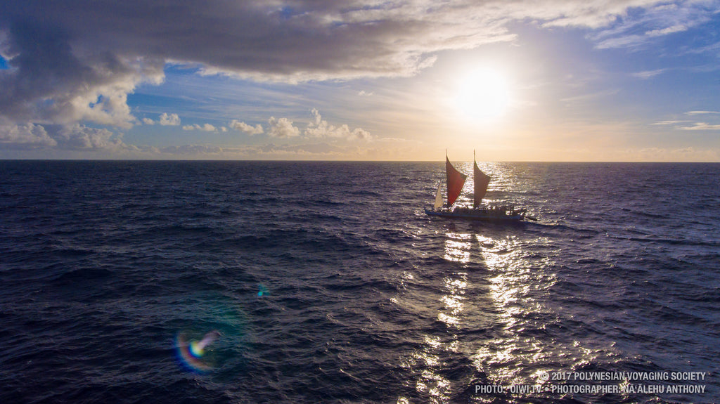 A drone shot of the canoe as it sails with the sun behind it, casting a shadow onto the water