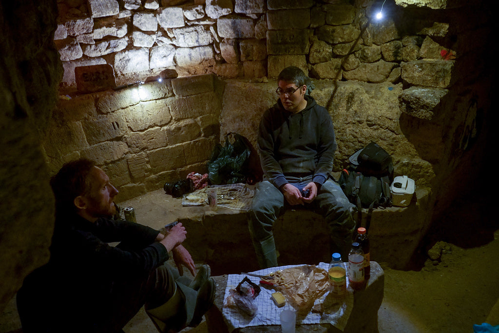 Two cataphiles having a picnic in the catacombs.
