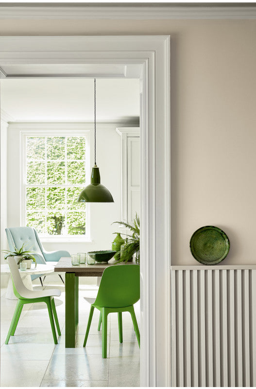 Calm dining room in Portland Stone with green furniture