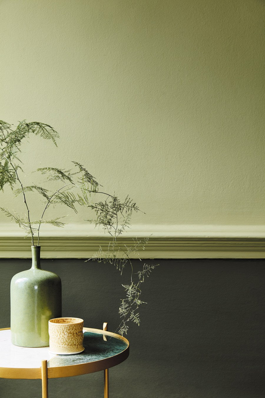 Different shades of green above and below dado rail with plants on table